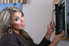 Woman using microwave. Pretty young woman in kitchen using microwave Royalty Free Stock Images