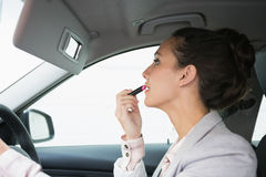 Woman using mirror to put on lipstick while driving Stock Image