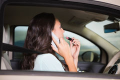 Woman using mirror to put on lipstick while on the phone Stock Photography
