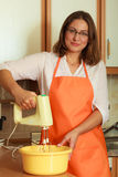 Woman using mixer in kitchen Royalty Free Stock Image