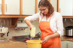 Woman using mixer in kitchen Stock Photography