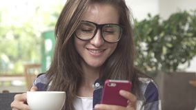 Woman using mobile cell smart phone laughing wearing glaasses and drink coffee stock video footage