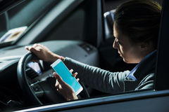 Woman using mobile while driving Royalty Free Stock Photos