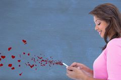 Woman using mobile phone against red hearts in background Stock Photography