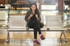 Woman using mobile phone in airport. JAKARTA - Indonesia. November 23, 2017: Asian woman playing games with a mobile phone while sitting on the chair in the Royalty Free Stock Photography