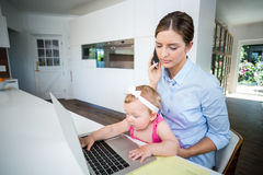 Woman using mobile phone and baby girl playing with laptop Royalty Free Stock Photos