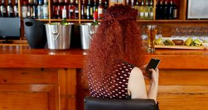 Woman using mobile phone in bar 4k. Rear view of woman using mobile phone in bar 4k stock video