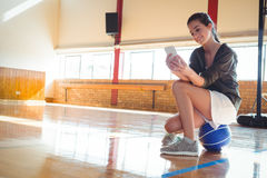 Woman using mobile phone in basketball court Stock Image