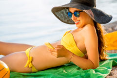 Woman using mobile phone on the beach Royalty Free Stock Photos