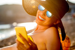 Woman using mobile phone on the beach Stock Photo