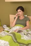 Woman using mobile phone in bed Stock Photo