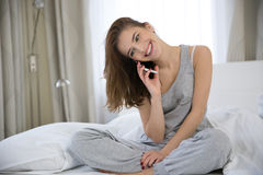 Woman using mobile phone in the bed Stock Image