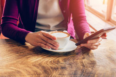Woman using mobile phone in cafe. Female holding cup Stock Image