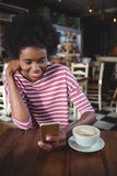 Woman using mobile phone in cafe Stock Image