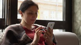 Woman using the mobile phone in cafe. On this video you see as the woman of the business woman sits in cafe. Hours of the woman in phone in a lunch break. The stock video footage