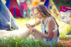 Woman using mobile phone at campsite. On a sunny day stock image