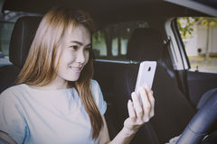 Woman using mobile phone in the car. Stock Images