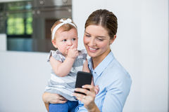 Woman using mobile phone while carrying baby girl Royalty Free Stock Image