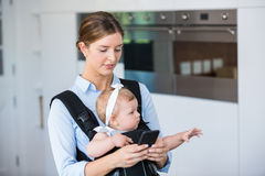 Woman using mobile phone while carrying baby girl Stock Photos