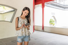 Woman using mobile phone in chinese garden Royalty Free Stock Photography