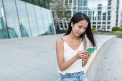 Woman using mobile phone in the city. Asian young woman Stock Photography