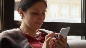 Woman using the mobile phone, Close plan. On this video you see as the woman of the business woman sits in cafe. Hours of the woman in phone in a lunch break stock video