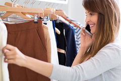 Woman using mobile phone in clothes shop Royalty Free Stock Photos