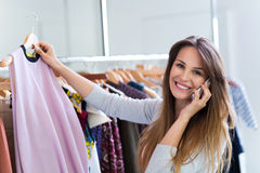 Woman using mobile phone in clothes shop Royalty Free Stock Image