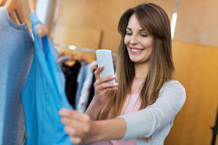 Woman using mobile phone in clothes shop Royalty Free Stock Photo
