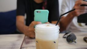 Woman Using Mobile Phone in Coffee Shop. Iced Coffee Drink Close-Up. HD Slowmotion Lifestyle footage. Thailand stock footage