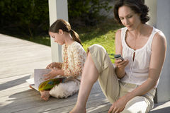 Woman Using Mobile Phone With Daughter Reading Book On Porch Stock Images