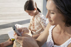 Woman Using Mobile Phone With Daughter Reading Book On Porch Royalty Free Stock Photos