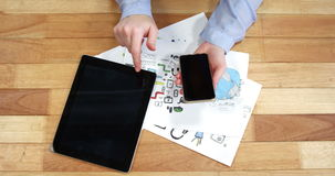 Woman using mobile phone and digital tablet while working at desk stock video