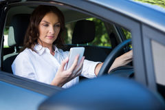 Woman using mobile phone while driving a car Royalty Free Stock Photos