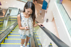 Woman using mobile phone on escalator Royalty Free Stock Photography