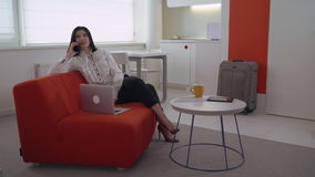 Woman using mobile phone in flat with white furniture. stock video