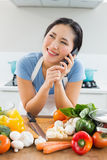 Woman using mobile phone in front of vegetables in kitchen Stock Images