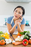 Woman using mobile phone in front of vegetables in kitchen Royalty Free Stock Image
