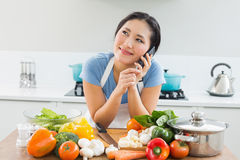 Woman using mobile phone in front of vegetables in kitchen Stock Photography