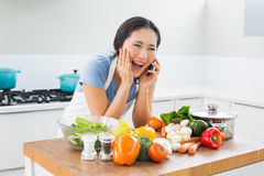 Woman using mobile phone in front of vegetables in kitchen Royalty Free Stock Photo