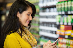 Woman using mobile phone in grocery section Stock Images