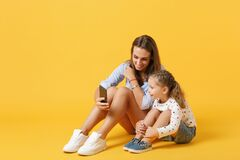 Free Woman Using Mobile Phone Have Fun With Cute Child Baby Girl 4-5 Years Old. Mommy Little Kid Daughter Isolated On Yellow Stock Images - 190256794