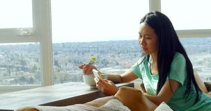Woman using mobile phone while having breakfast in living room 4k. Woman using mobile phone while having breakfast in living room at home 4k stock video