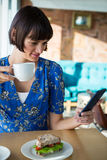 Woman using mobile phone while having coffee Royalty Free Stock Image