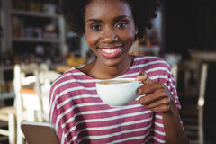 Woman using mobile phone while having cup of coffee Stock Image