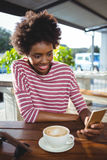 Woman using mobile phone while having cup of coffee Royalty Free Stock Images