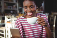 Woman using mobile phone while having cup of coffee Stock Photo