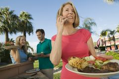 Woman using mobile phone holding plate of food at family outdoor barbecue. Royalty Free Stock Image