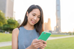Woman using mobile phone in Hong Kong sunset. Asian young woman portrait Royalty Free Stock Images
