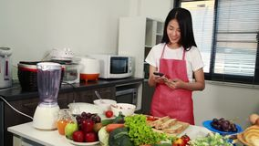 Woman using mobile phone. In kitchen room stock footage